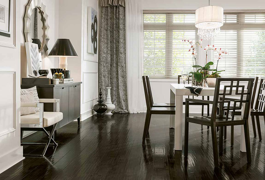 Dining room decorated with modern dining room decor on espresso wood floors and white and grey curtains covering windows.