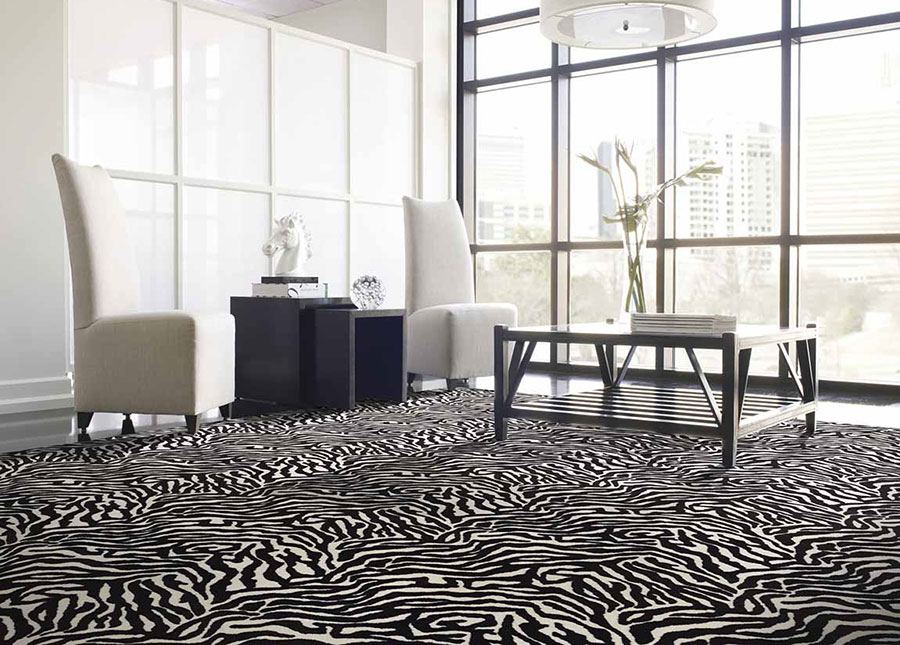 Living room with white high back chairs and black end tables on black and white zebra print rug.